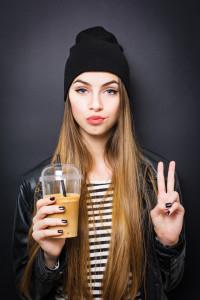 Beautiful urban teenage girl with takeaway coffee gesturing peac